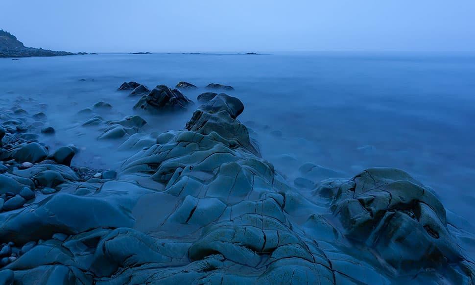 coastal water and rocks at dusk blue hour