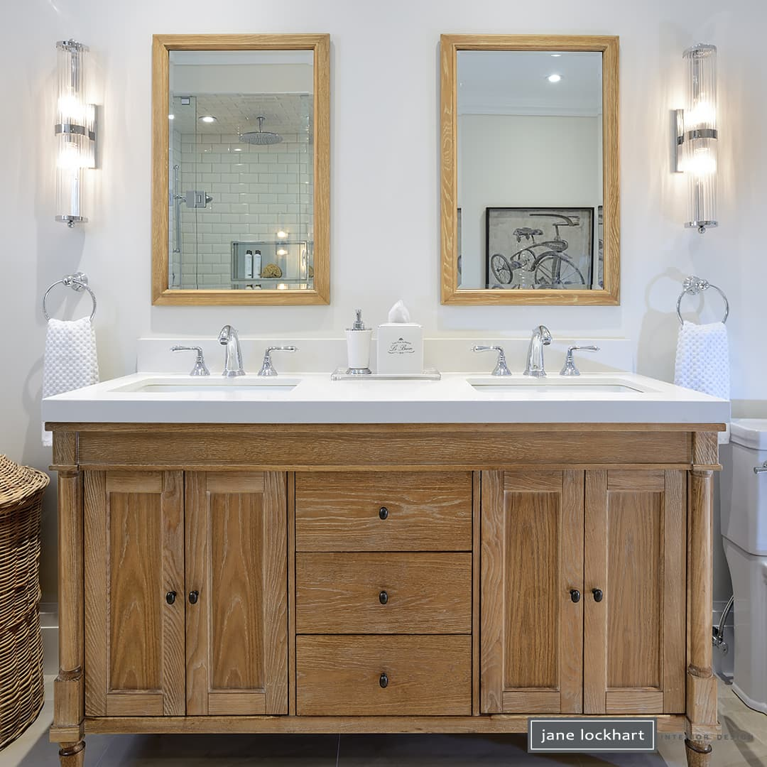 bathroom with white walls, two sinks and two mirrors