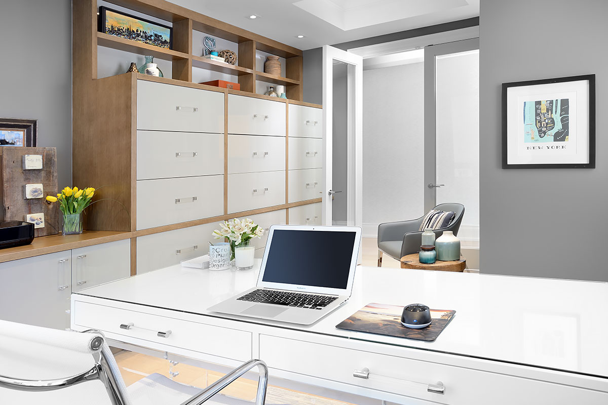 Custom built cabinetry lines the wall of this modern office it carries the solid wood with white drawer front theme seen in the kitchen