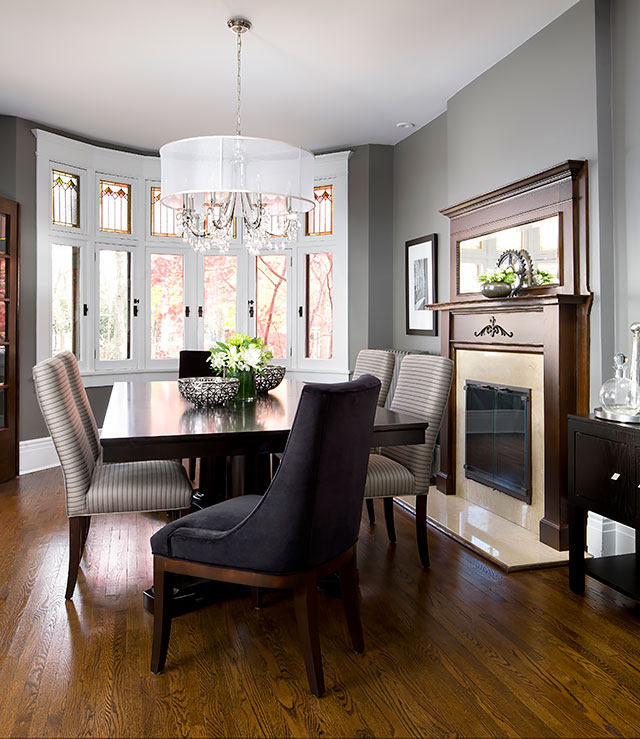 The dining rooms modern furnishings and shaded chandelier are framed beautifully by the classic leaded windows and beautifully refinished fireplace